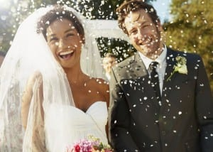 Shot of a happy newlywed couple being showered with confetti