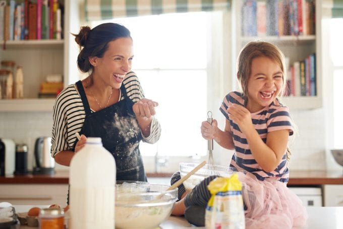 little girl having fun baking with her mother in the kitchen
