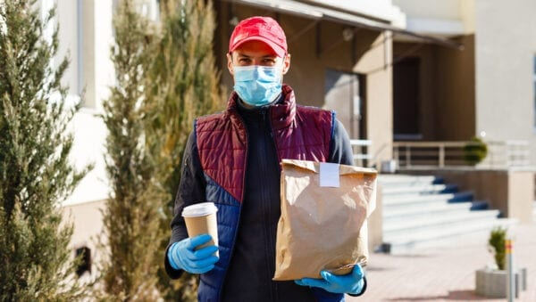 Courier in protective mask and medical gloves delivers food.